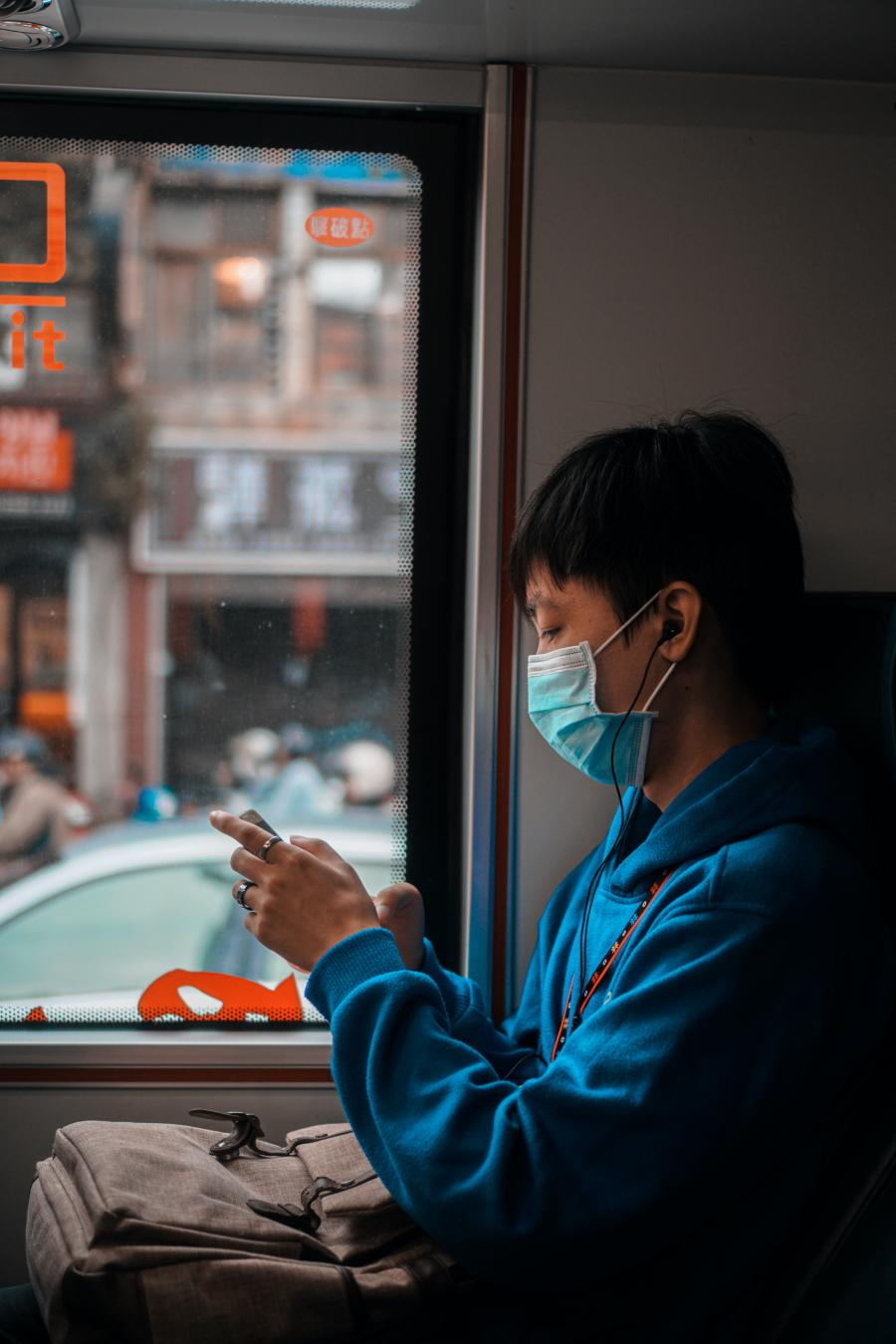 a person wearing a mask uses their phone on a bus
