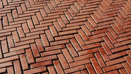 Close-up view of a brick walkway laid out in a herringbone pattern
